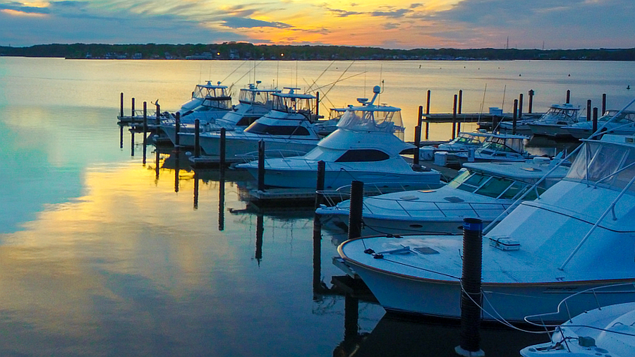 Boats anchored in a harbor during sunset.
