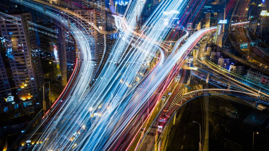 Nighttime long exposure aerial image of a busy urban highway network.
