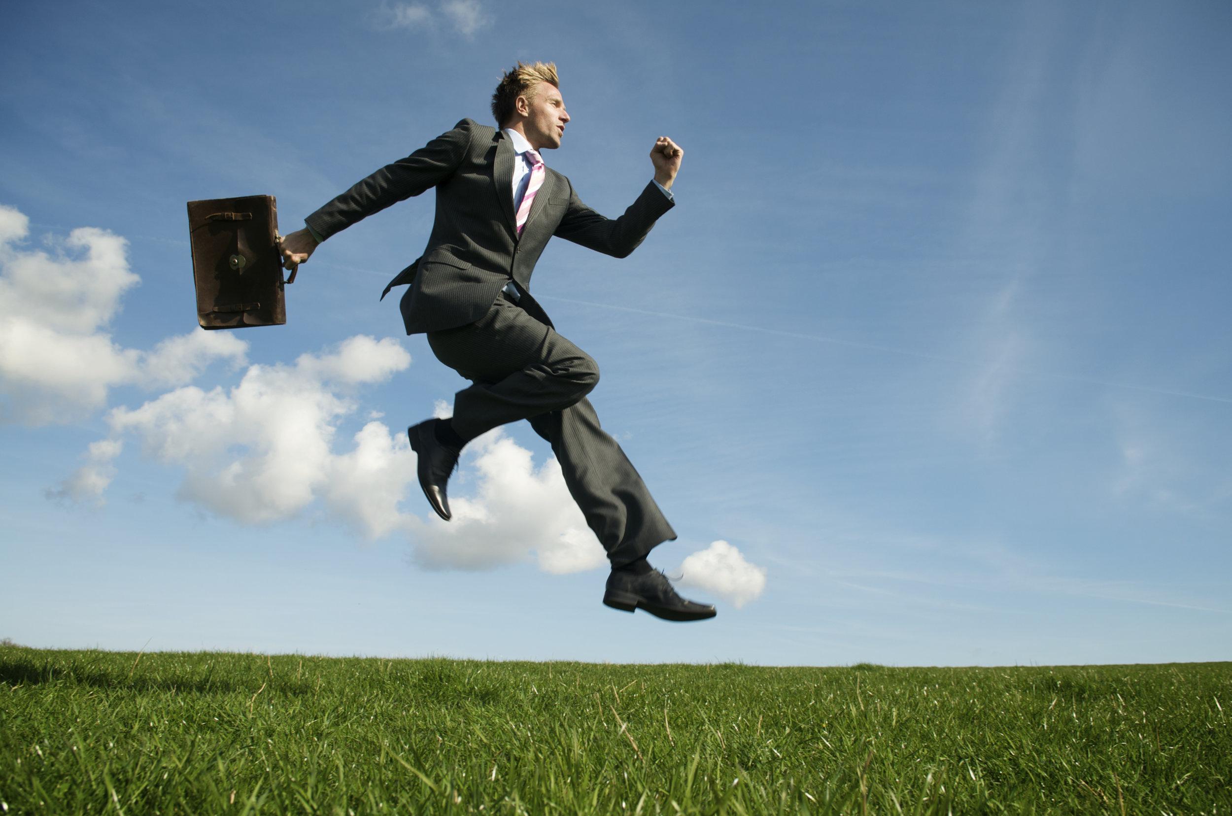 Businessman jumping on grass.jpg