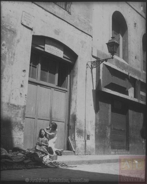 Dos niñas frente a la puerta de la Casa de Dormir. A su lado, en el número anterior de la calle Cid, la fachada de La Criolla cerrada con una verja