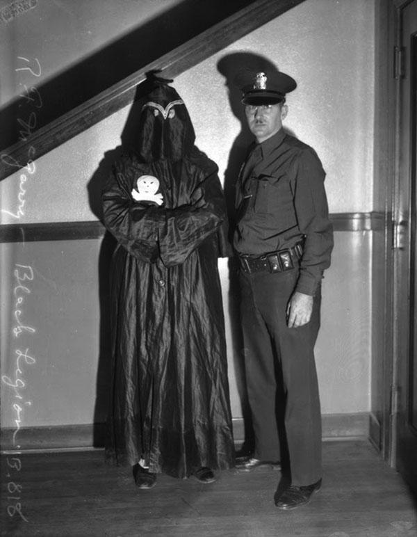Un policía posa junto a un detenido de la Legión Negra