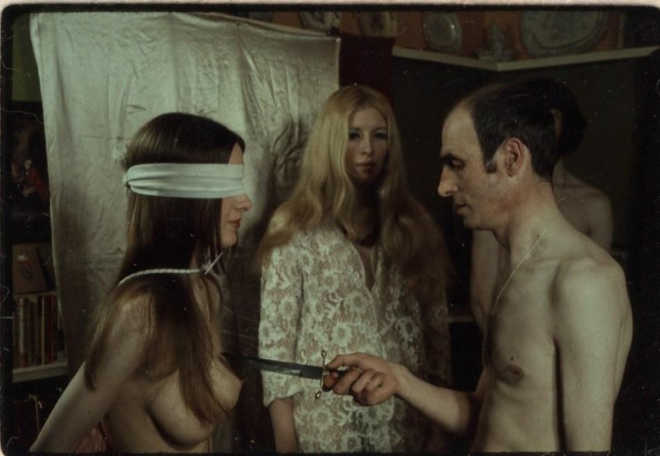 Alex Sanders con un cuchillo en medio de un ritual. Al fondo, su compañera Maxine