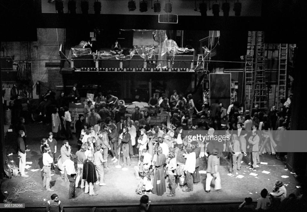 Arriba, Ben Morea (sentado y con barba), antes de tomar la palabra y okupar el Fillmore. La persona que está detrás sentada es el propio Bill Graham. Abajo, en el centro, Morea toma la palabra en medio del caos y con el público en el escenario. Fotografías: Bev Grant
