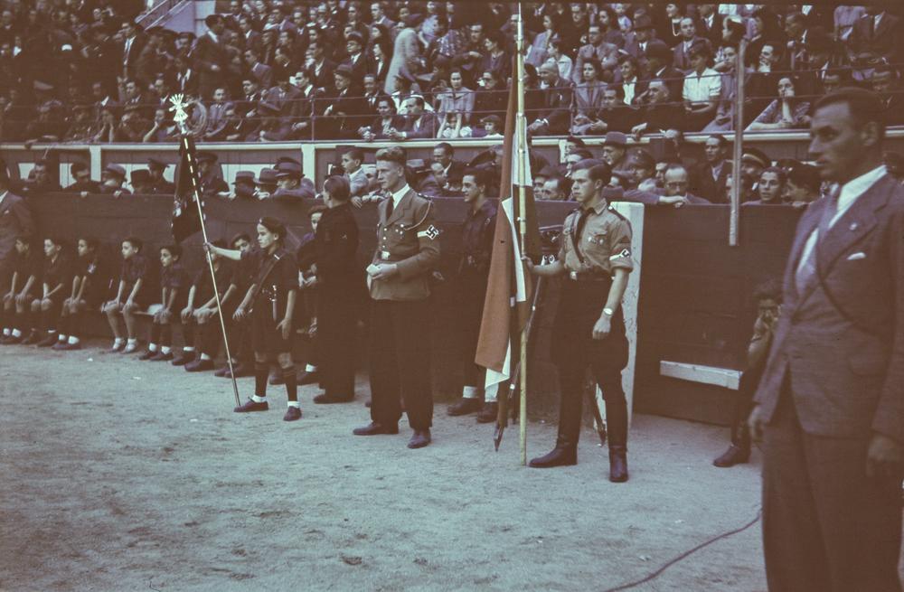 Farbfilm [Película en color. Muchacho de las Juventudes Hitlerianas sosteniendo una bandera de cruz gamada junto a un niño del Frente de Juventudes que sostiene una bandera falangista en la arena de la plaza de toros de las Ventas. Público en las gradas] . 20 de octubre de 1940. otto wunderlich.