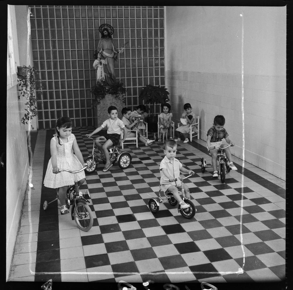 Centro Maternal de la Cárcel de Mujeres [Interior de una cárcel de mujeres, sala presidida por una escultura de San José con el Niño, pavimento ajedrezado y paredes con zócalo azulejado, un grupo de niños montan en triciclo en el interior mientras otros. fotografía: pando barrero