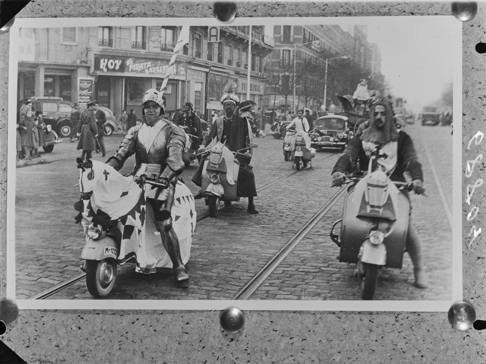 Desfile de motocicletas Vespa por una calle, posiblemente madrileña. Los pilotos visten disfraces medievales (29 de mayo de 1956). Fotografía: Pando barrero