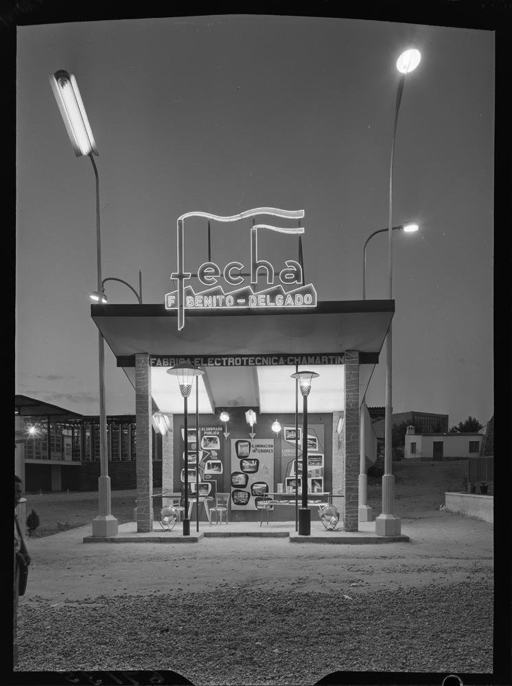 Stand en la Feria del Campo. Stand informativo con cubierta plana inclinada sobre pilares y cerramiento trasero. Pertenece a la Industria Eléctrica Francisco Benito Delgado S.A. En el interior se dispone una mesa con sillas para atender a los clientes (1956). Fotografía: Pando Barrero.