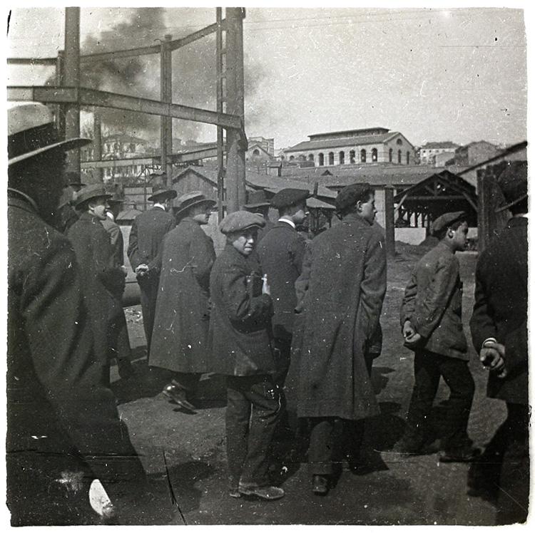 Obreros madrileños en 1920. Hombres y niños con abrigo, boina y sombreros entrando a la fábrica. Fragmento de placa esterescópica. Foto: Cano.