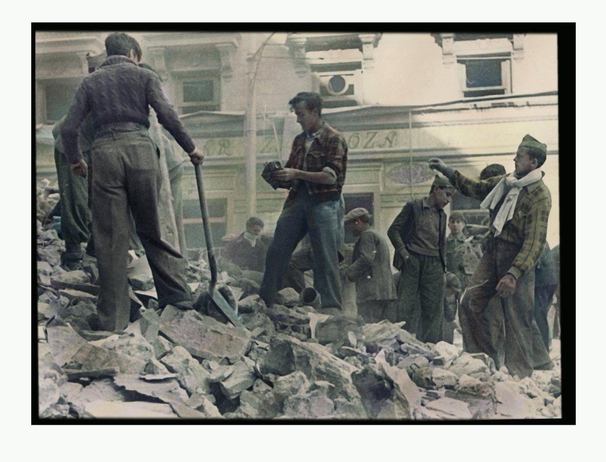 Entre los encombros del edifico bombardeado de la Farmacia el Globo en la Plaza de Antón Martín de Madrid en el invierno de 1936. Foto Robert Capa. Archivo BNE. Coloreada