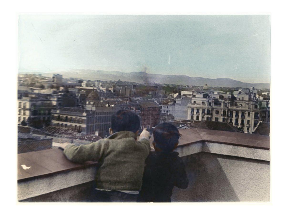Dos niños observan un bombardeo desde una terraza de un edificio del Barrio de Salamanca de Madrid. Uno señala con el dedo una columna de humo posiblemente en la zona de Cuatro Caminos o Tetuán. ca 1936. Foto David Seymour. Archivo ICP. Coloreada