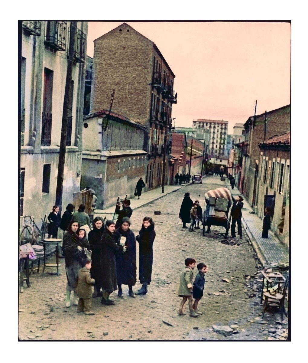 Tras un bombardeo en el barrio de Vallecas, la gente desaloja los enseres que pueden y se preparan para marcharse tras quedarse sin casa. Refugiados. 1936. Foto Archivo BNE. Coloreada