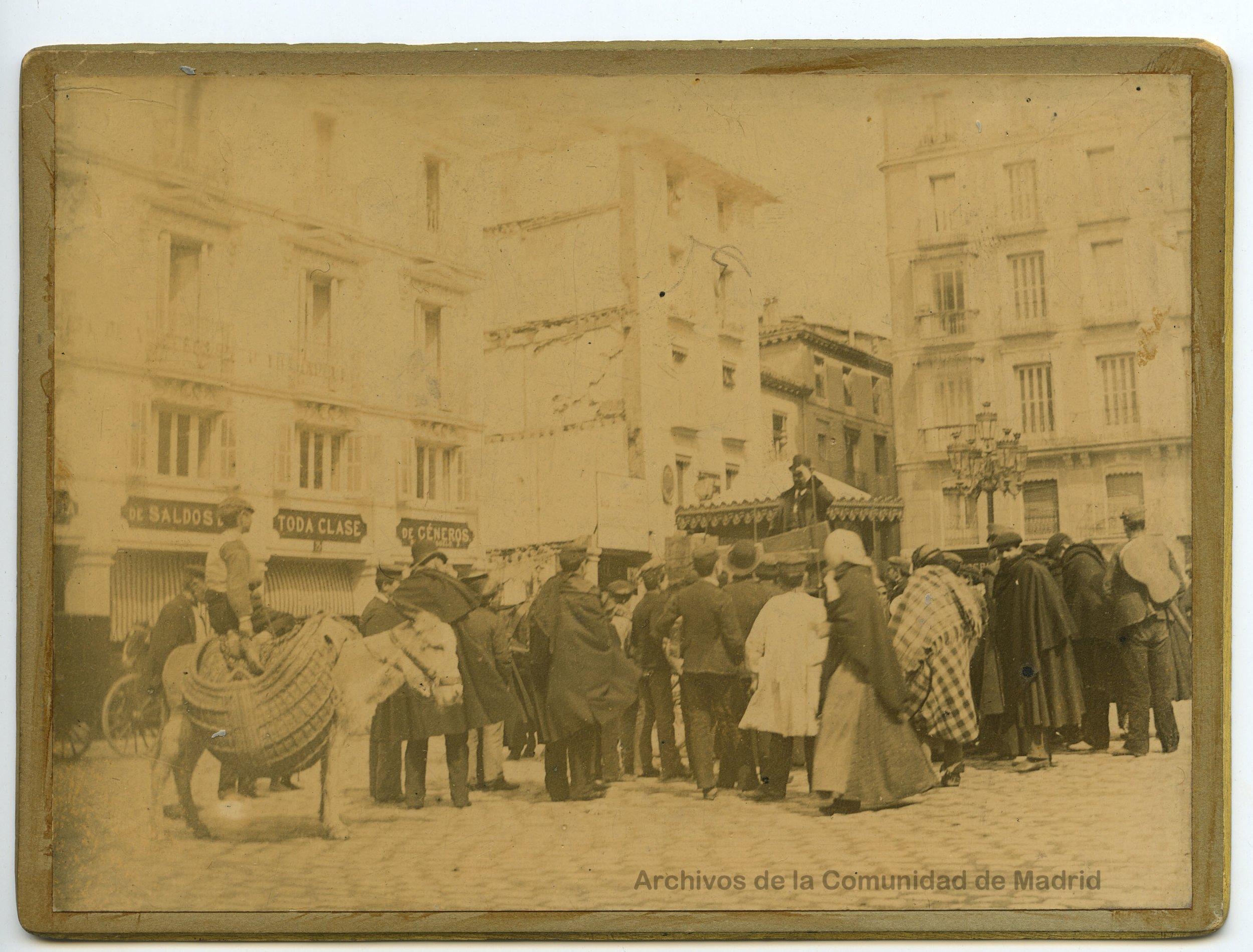 Charlatán subido en un entarimado, en la plaza de Santa Cruz, 6 con vuelta a la calle San Cristóbal, reunidos ante él, distintos personajes del Madrid más castizo, destacando un hombre encima de un borrico con alforjas de esparto (1890). Fotografía: Juan Moya
