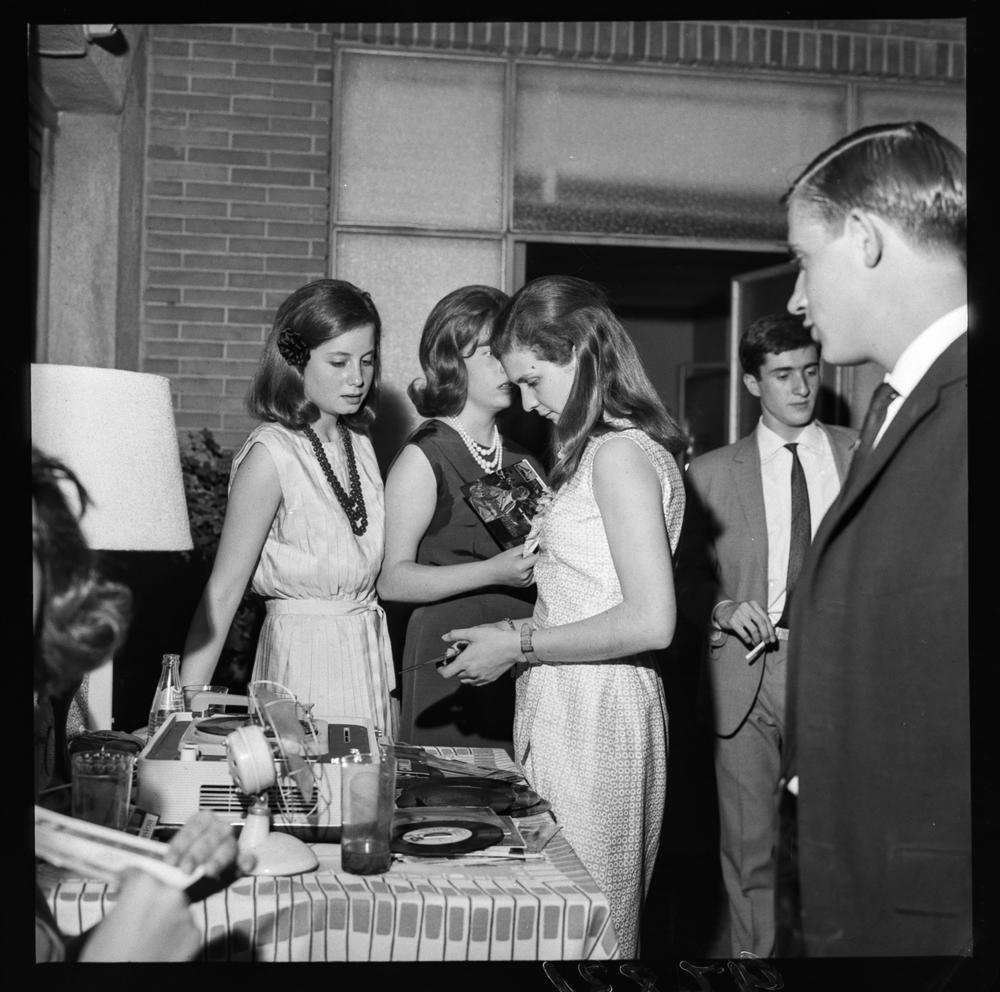 Grupo de jóvenes al pie de una mesa con un tocadiscos durante una fiesta. Posiblemente años cincuenta-sesenta. Fotografía: Pando