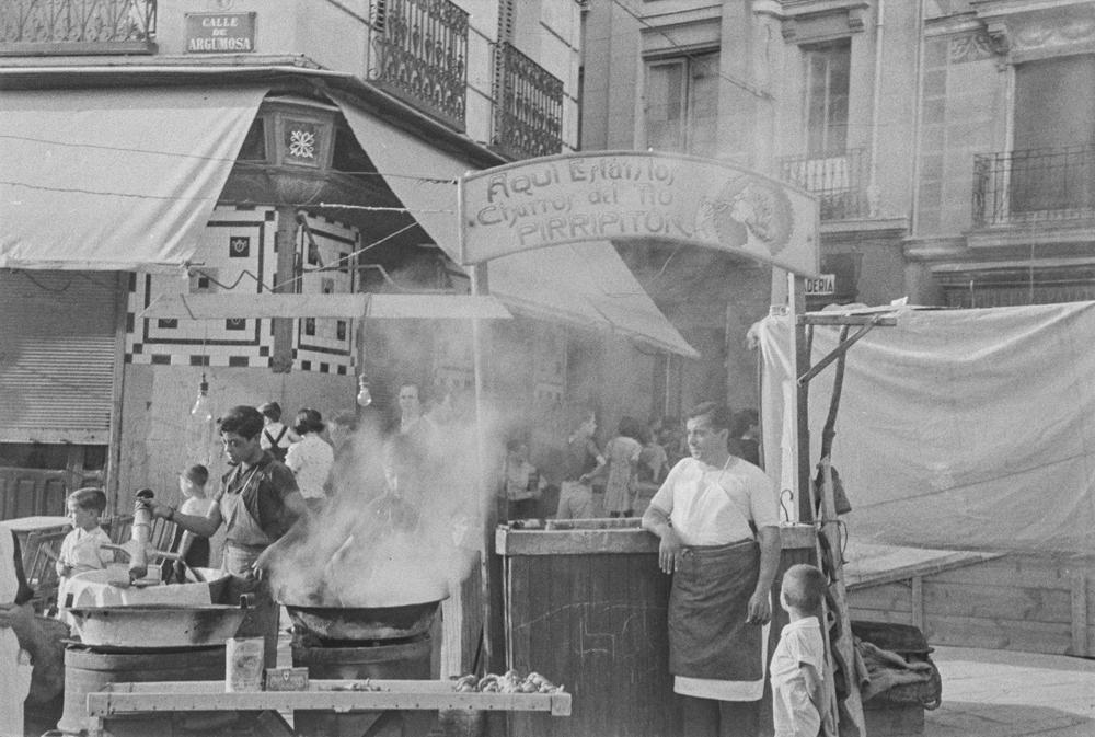Agosto de 1940. Verbena Lavapiés. Puesto de churrero en la calle Argumosa con dos jóvenes friendo los churros y hombre fumando apoyado en el mostrador. Fotografía: Wunderlich