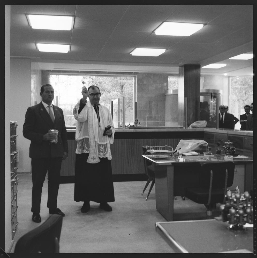 Bendición del Banco Guipuzcoano [Sacerdote católico salpica agua bendita en las oficinas de una sucursal bancaria]. Años cuarenta. Fotografía: Pando