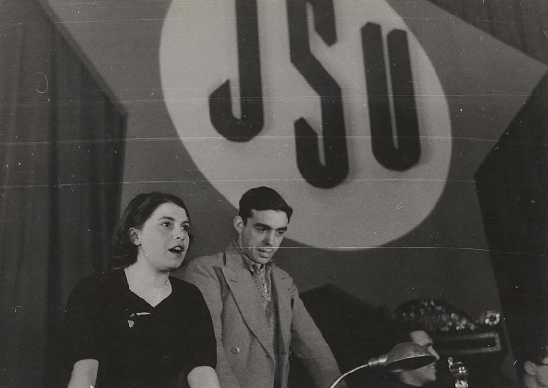 Trifón Medrano, de pie y a la derecha de la oradora, durante un acto de las JSU