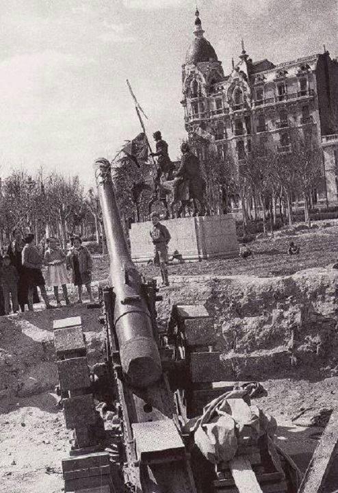 Sancho Panza sostiene una bandera republicana en el monumento al Quijote de la Plaza de España (Madrid), mientras los cañones apuntan al Cuartel de la Montaña, que está justo enfrente (1936)