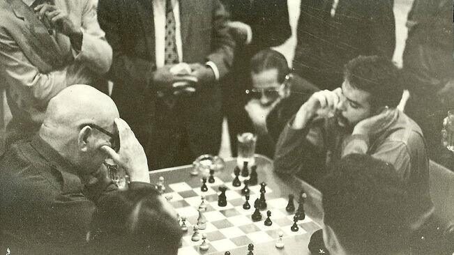 Bayo, a la izquierda, juega al ajedrez con el Che bajo la atenta mirada de Raúl Castro, sentado junto a él