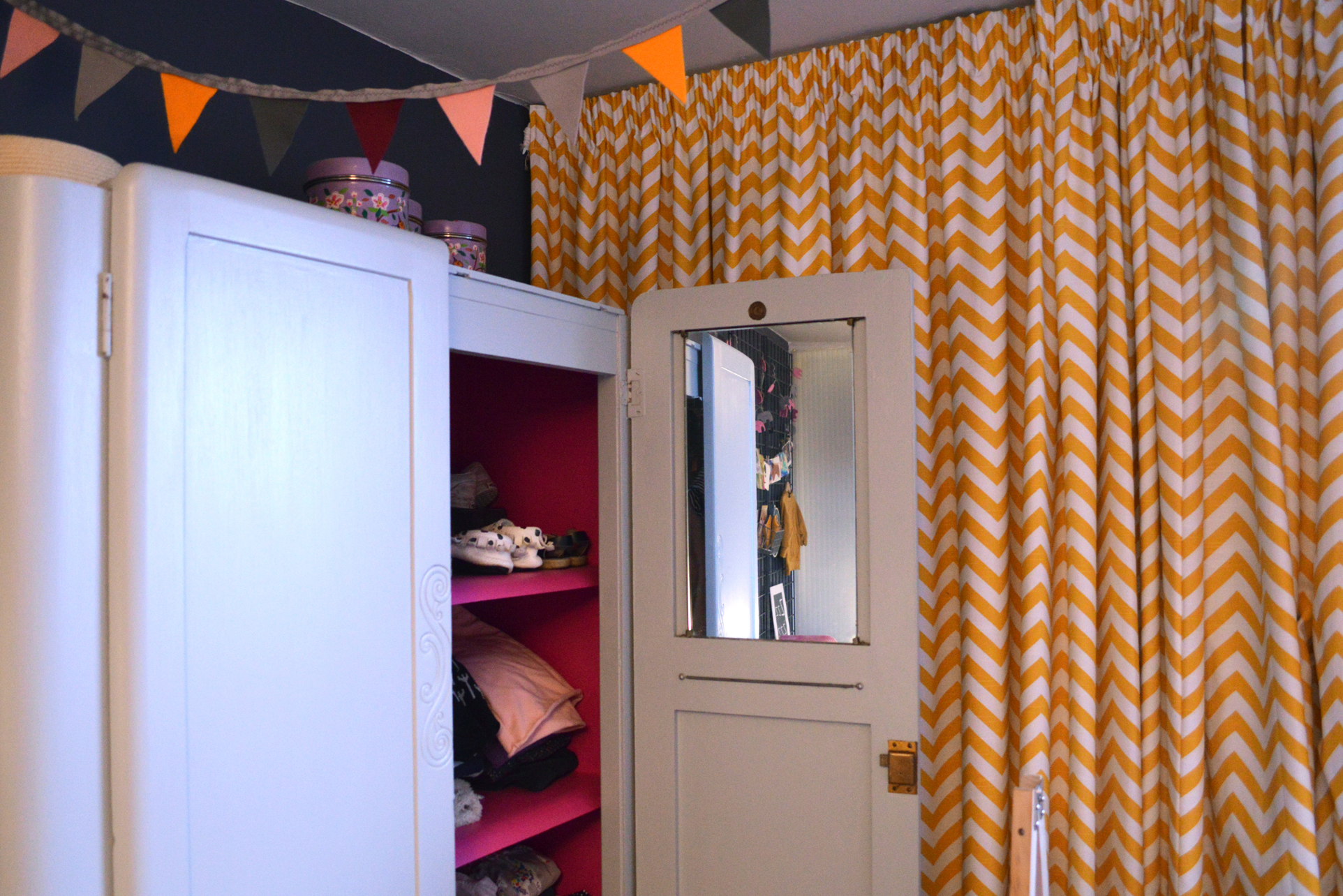 The hot pink charity-shop-find wardrobe interior is a cool concession to girliness