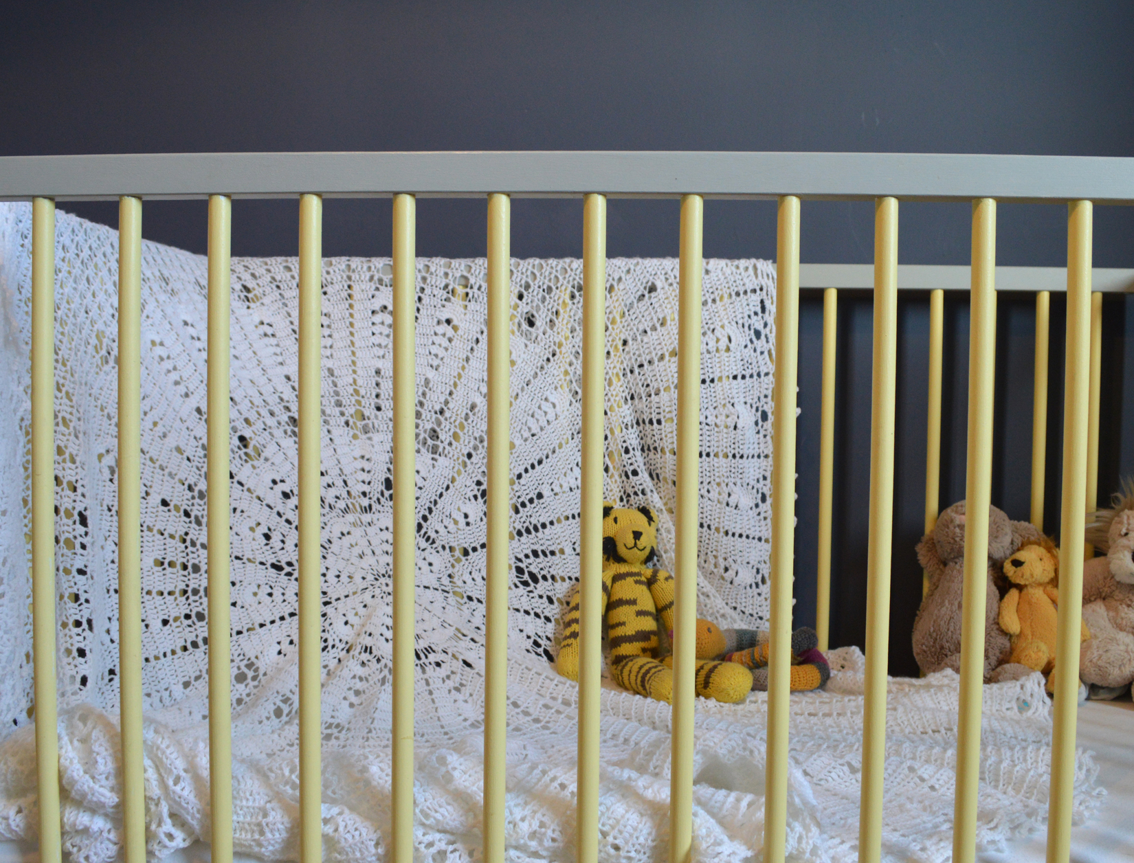 The Ikea cot is painted in Farrow & Ball's Day Room Yellow and Manor House Gray