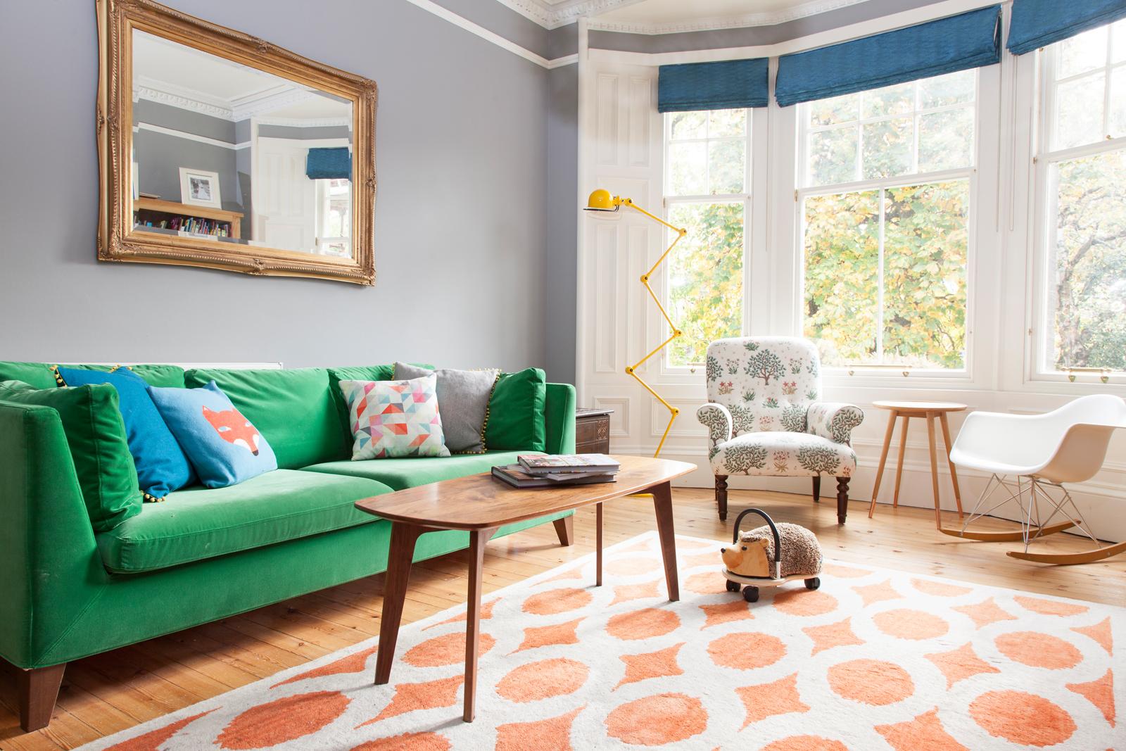 Grey walls make the green velvet sofa look more vibrant/Photo: Susie Lowe