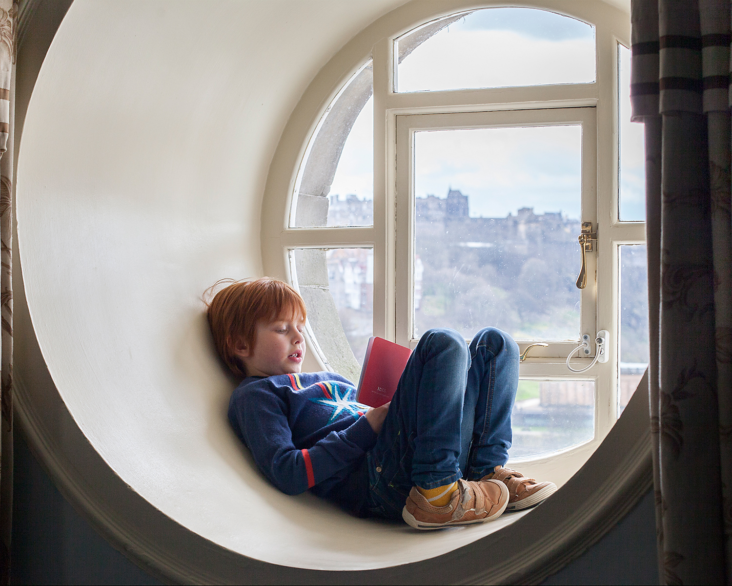 So  that's  what's through the round window:Oscar and his hotel 'passport', with Edinburgh Castle in the background