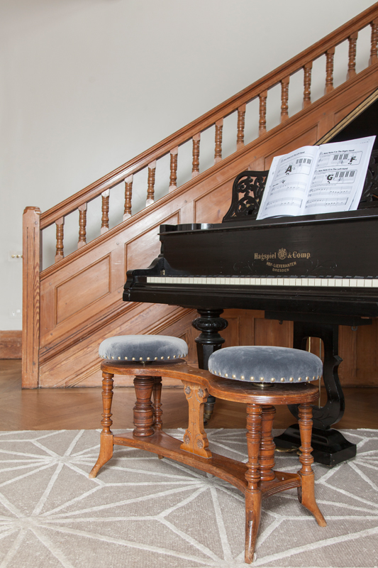 Grand piano with vintage double stool reupholstered in grey velvet/Photo: Susie Lowe
