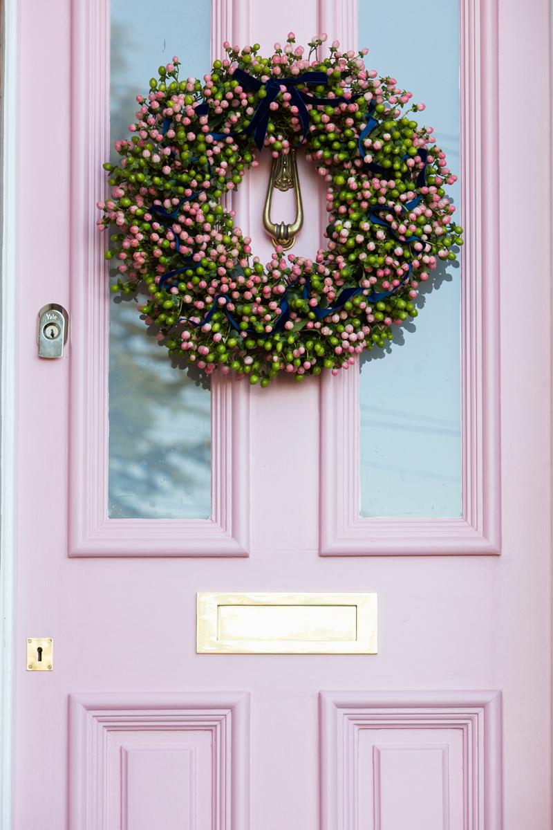Pink hypericum berries wreath on pink front door