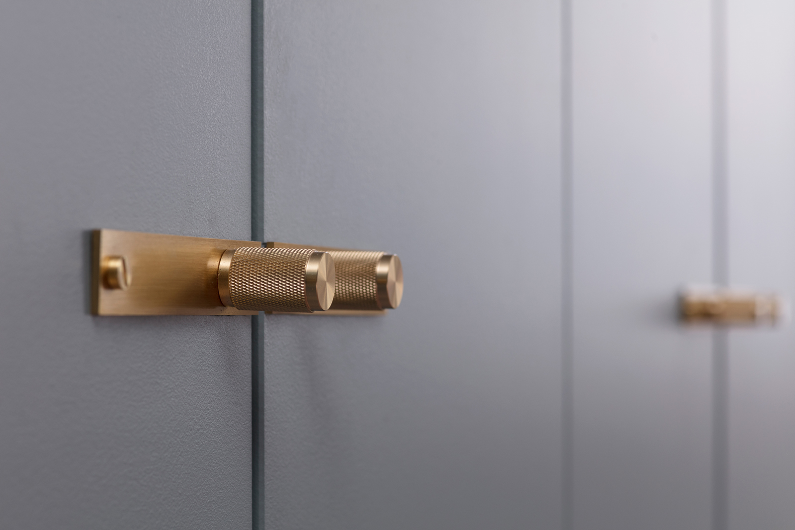 Buster + Punch brass handles on a blue fitted wardrobe