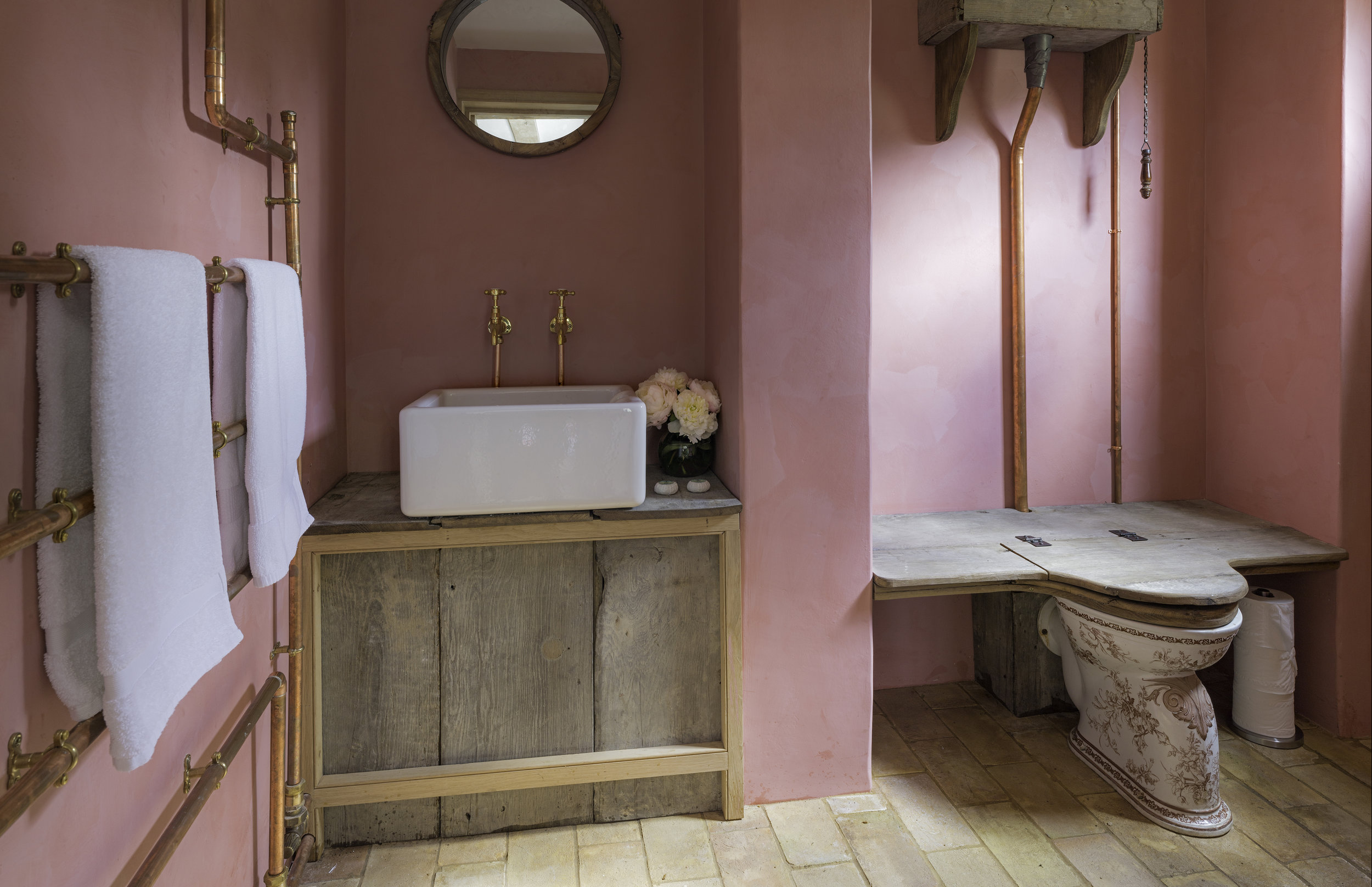 Pink, weathered wood and copper pipes combine in the Farmhouse bathroom