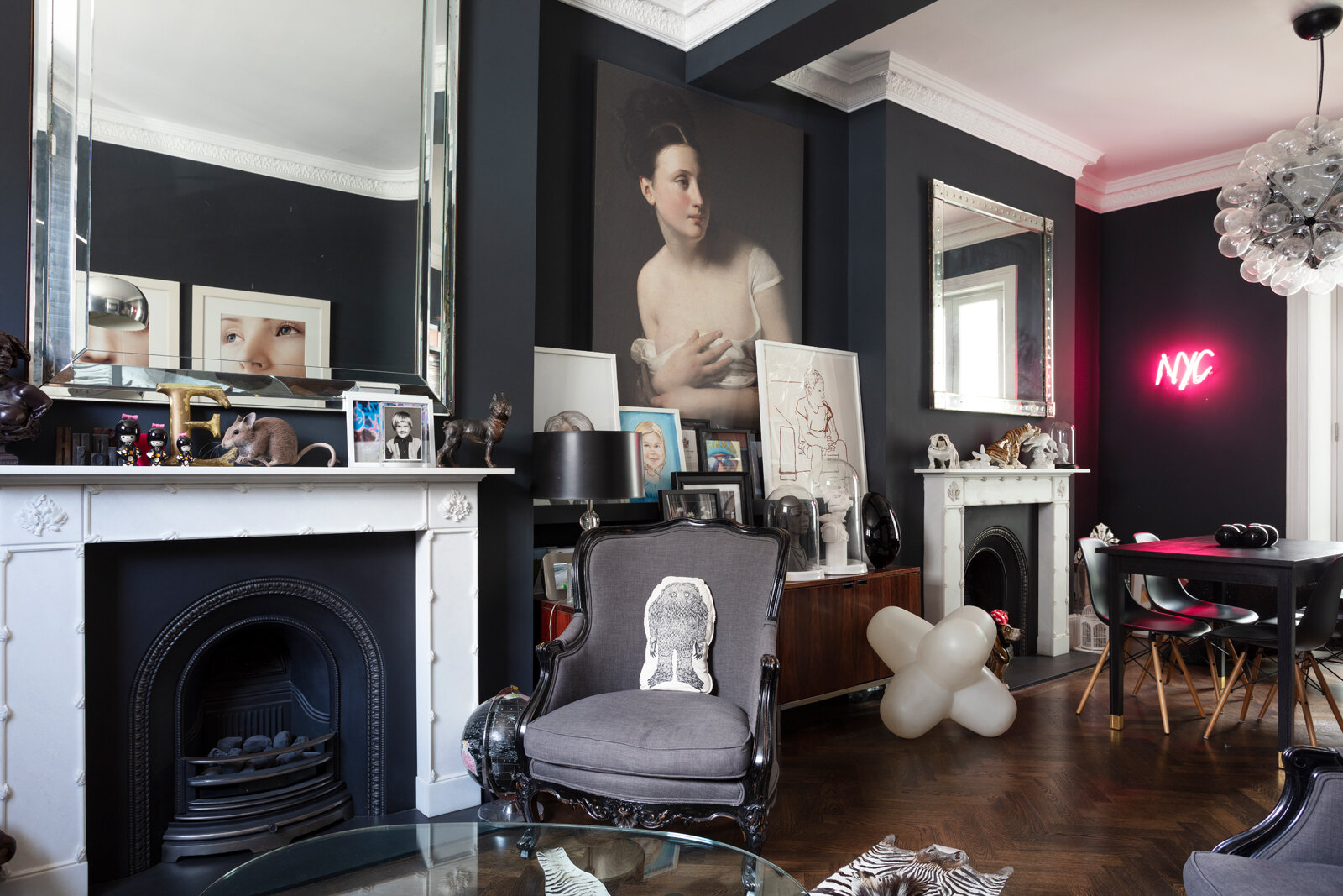 Black sitting room painted in Farrow & Ball's Railings with pink neon sign