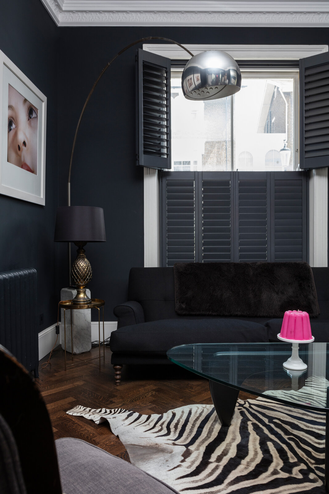 Black sitting room with shutters and zebra skin rug