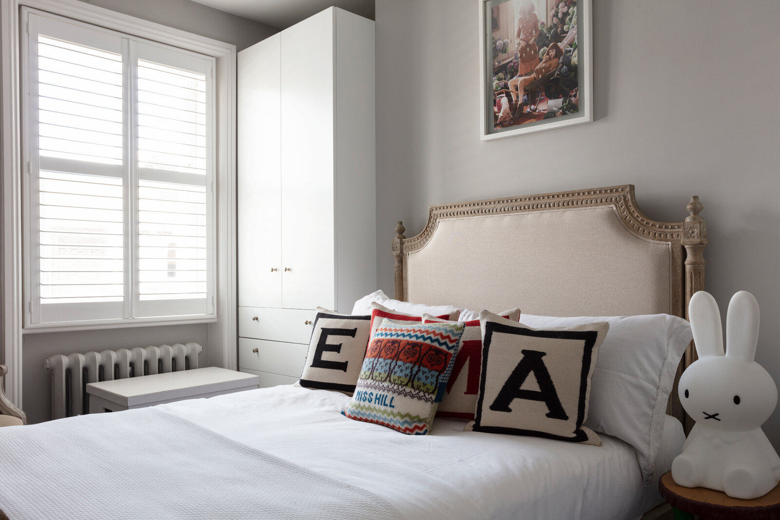White spare room with alphabet cushions and fancy headboard