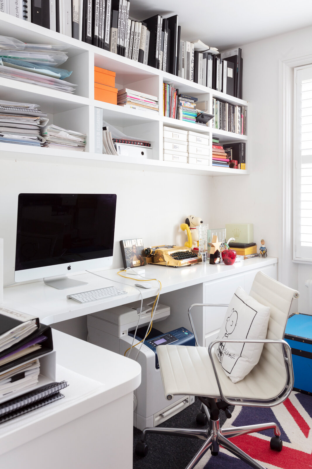 All white home office with gold typewriter and display shelves