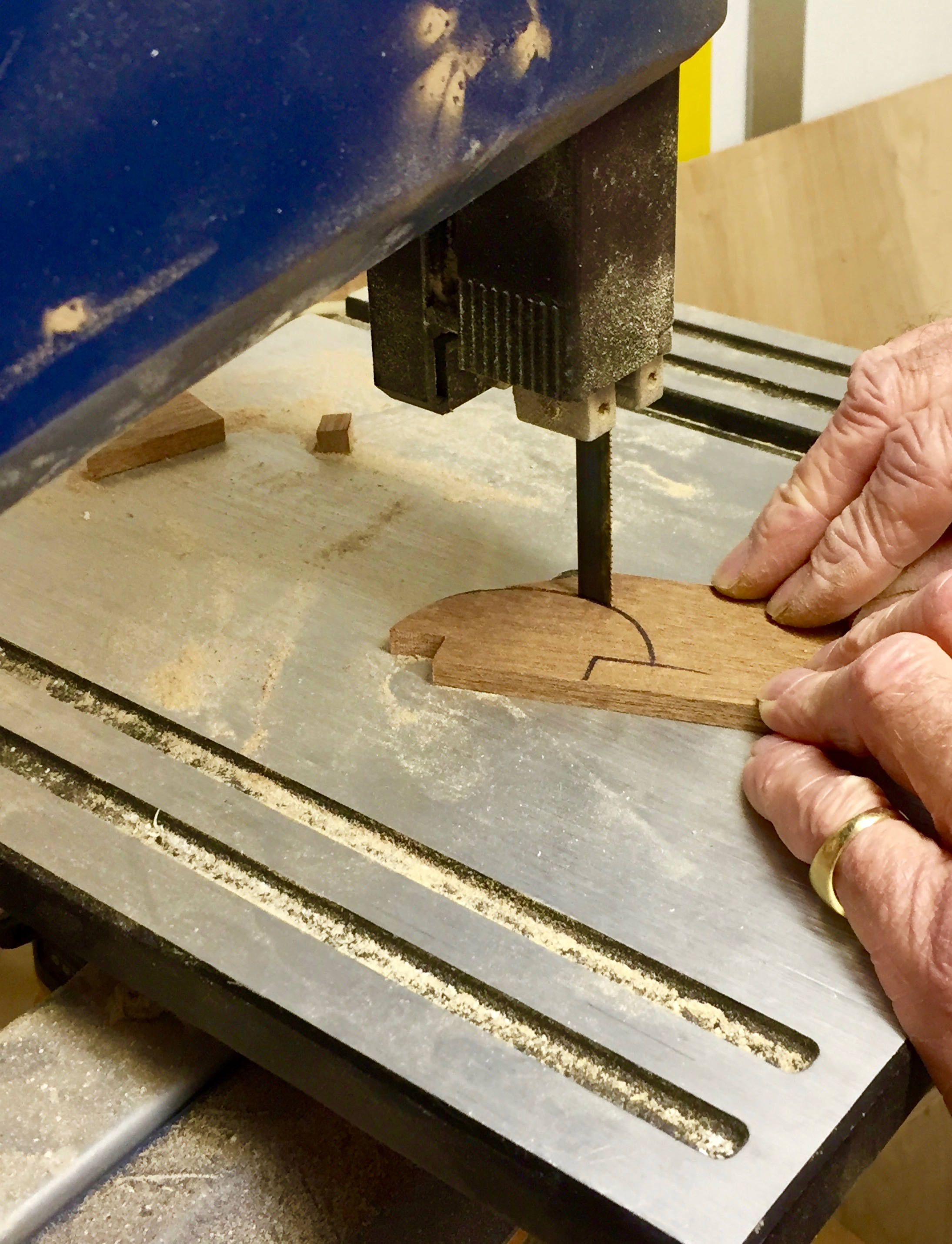 Cutting mahogany handles for Mardi Gras cabinets.