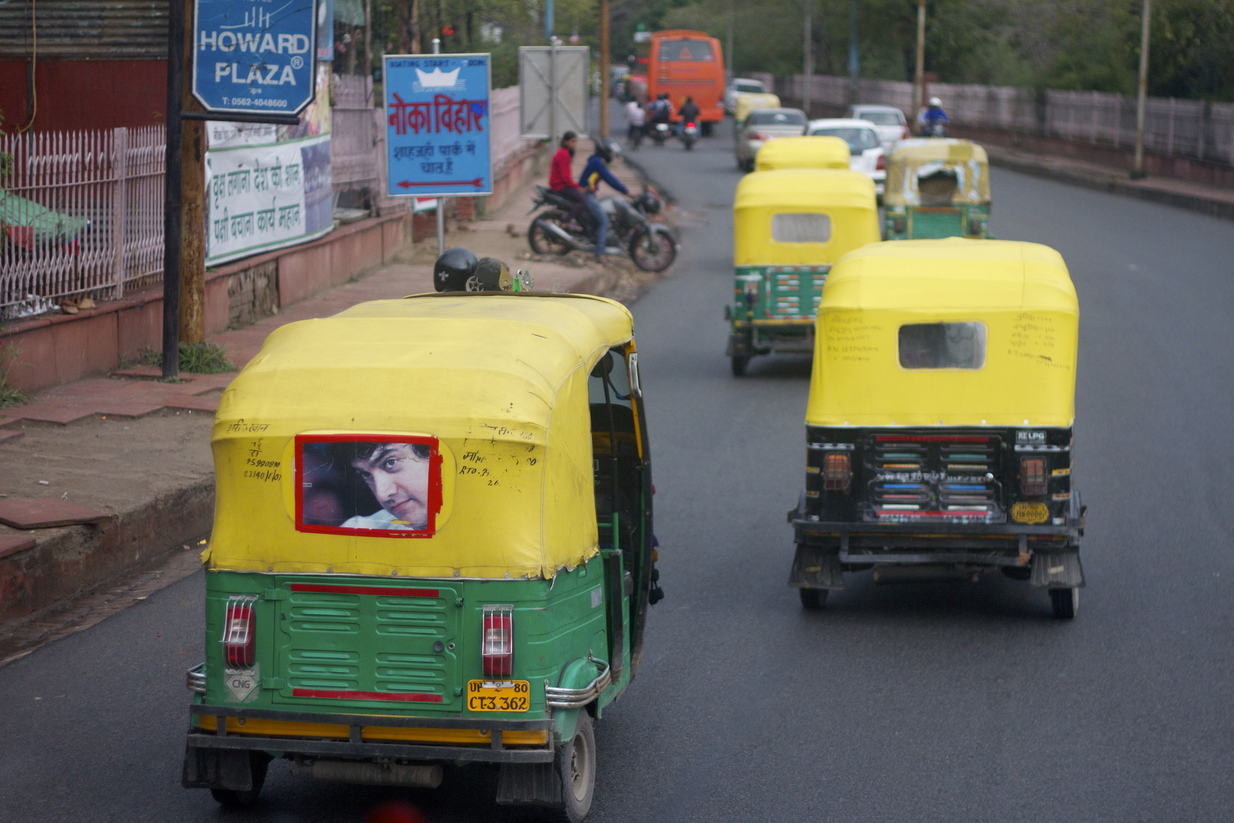 Tuk tuks drive through the streets of New Delhi, India.