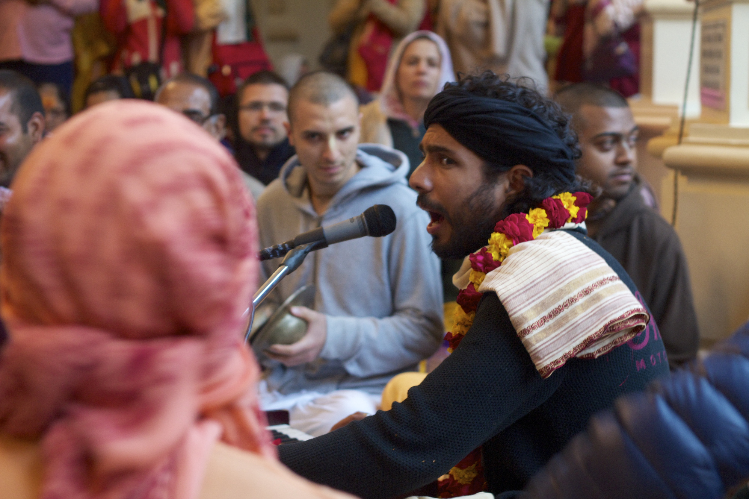 A musician leads a Hare Krishna chant among devotees in the ISKCON mandir in Vrindavan, India.
