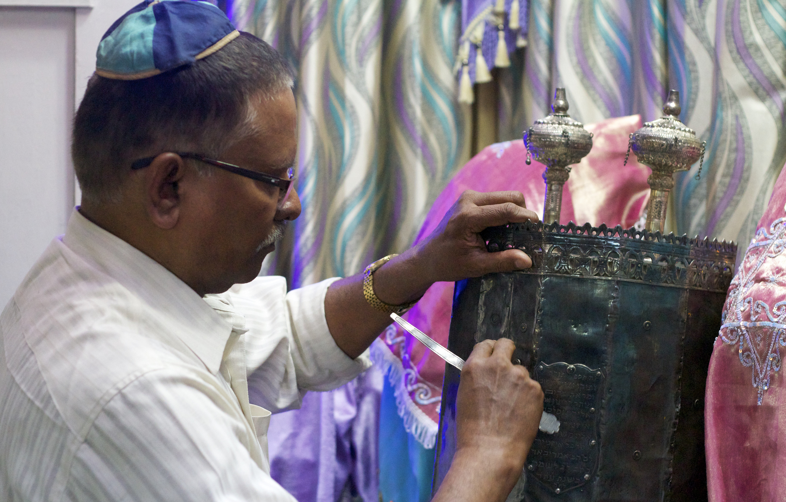 A man secures the Torah in the Magen Abraham Synagogue in Ahmedabad, India.