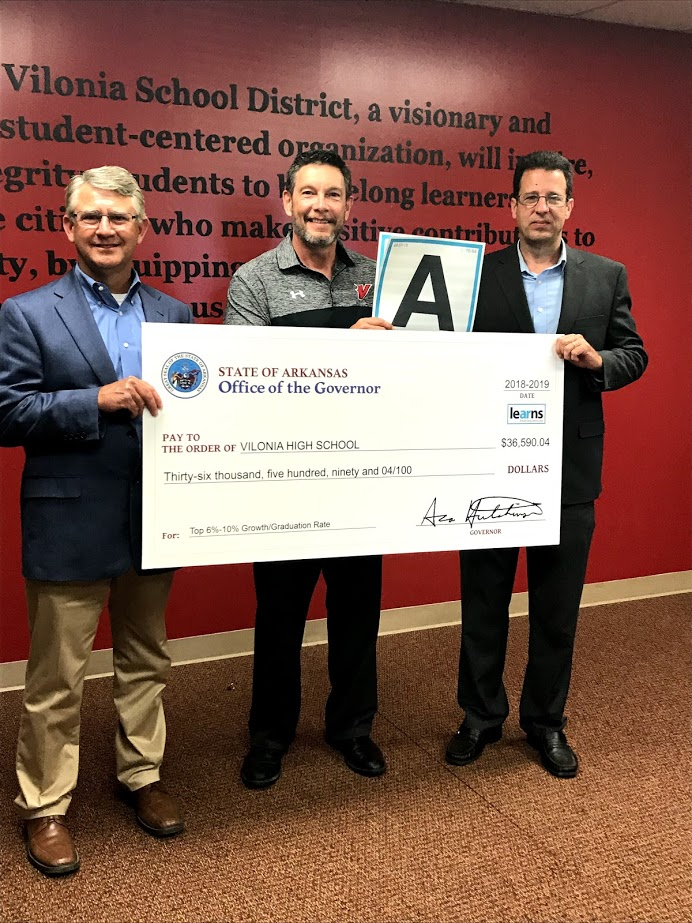 3 men holding a large check