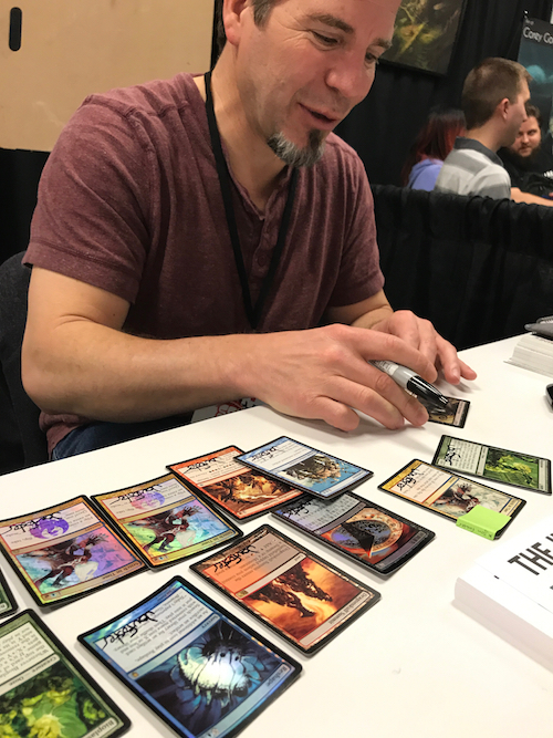 Jon Foster signing Magic the Gathering cards at our Booth.
