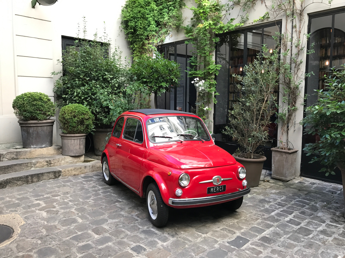 Tiny, vintage red car outside of fun home goods and fashion store, Merci.