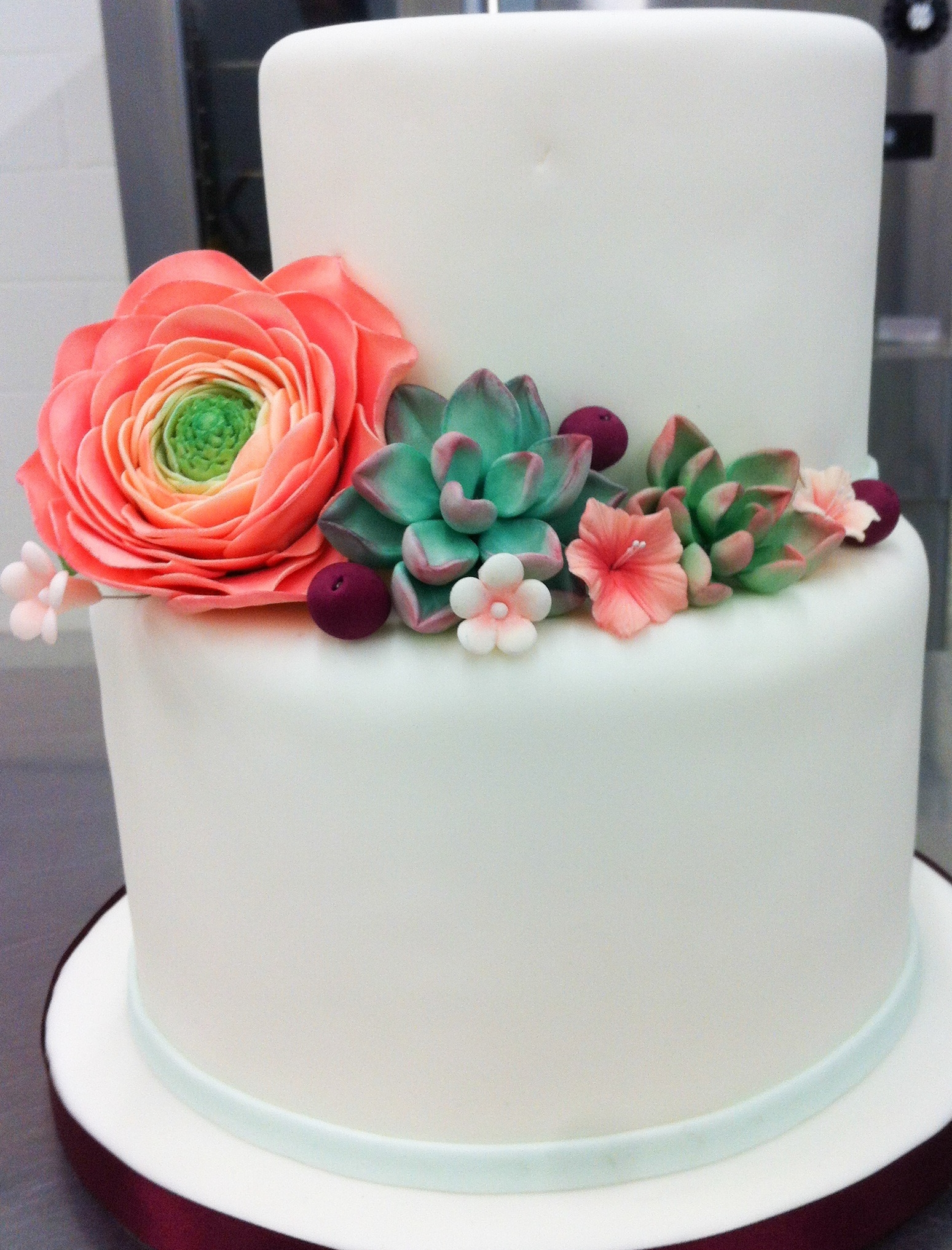 White fondant cake with handmade flowers and succulents