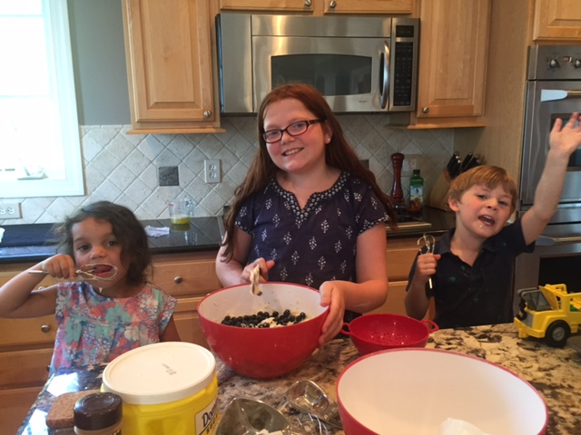 Ava (center) teaches Asha (left) and Will how to make some delicious muffins while exploring math concepts in the process.