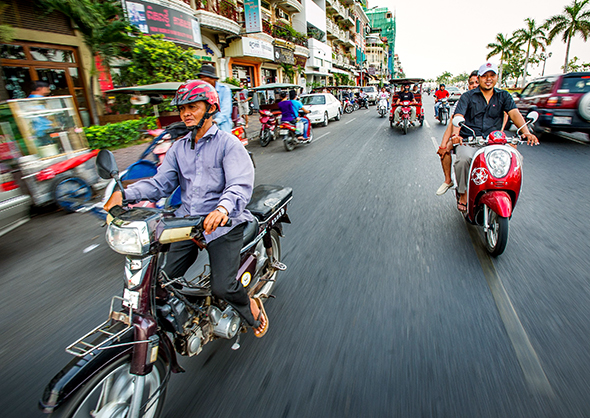 Motorcyclists ride along Preah Sisowath Quay—and the Tonlé Sap River—in Cambodia's capital city, Phnom Penh. (Photograph by Eric Reed, Corbis)