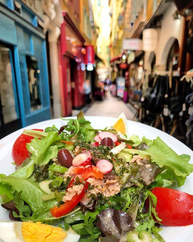 "Nicoise Salad in the town that made it a ""thing"". 🥗 We spent several days trying to figure out what is Nicoise cuisine?! It's not just this famous salad of tuna, egg, olives, tomato, & anchovy. Nicoise menus are also highly influenced by the Italians who occupied the city until 1861 (thanks google) so you'll find lots of fresh pastas & pizza. 🍝 Plus a delicious local dish called Socca which is a cross between a tortilla & flatbread and made out of ground chickpea flour- super flavorful, soft & yummy. I could eat Socca every day (swipe to see). There's also an onion & anchovy pie which is local to Nice. 🥧 We loved exploring new food experiences and we both excited for some healthy home cooking when we get back to NYC (maybe with some French cheeses in our fridge more often 🧀)."