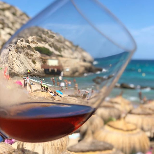 Seeing the world through a wine lens. One of the pioneers of quality wines in #Mallorca, @vinosferrer Jose Luis Ferrer still lives up to it's indigenous recipe of using authentic grapes in their wines. In this deep salmon turning ruby #roséwine the producer has used a blend of local mallorcan #grapes Mantonegro, Callet, Tempranillo along with locally grown Cabernet Sauvignon & Syrah. The colour may say one thing, but the wine is still on the lighter side, with soft and supple tannins perfect to suit #summerroasts lightly grilled. This... against the blue sea landscape is meant to cool off the hot breeze #summerwine #beachwine. Drink it young @vinos.ferrer . .  #labourday #summertime . . . #sumiliertasting #wines #winetasting #winestagram #mallorca🌴 #beachwine #instavino #grapesofspain #vino #travelphotography #beachtime #sundaystory