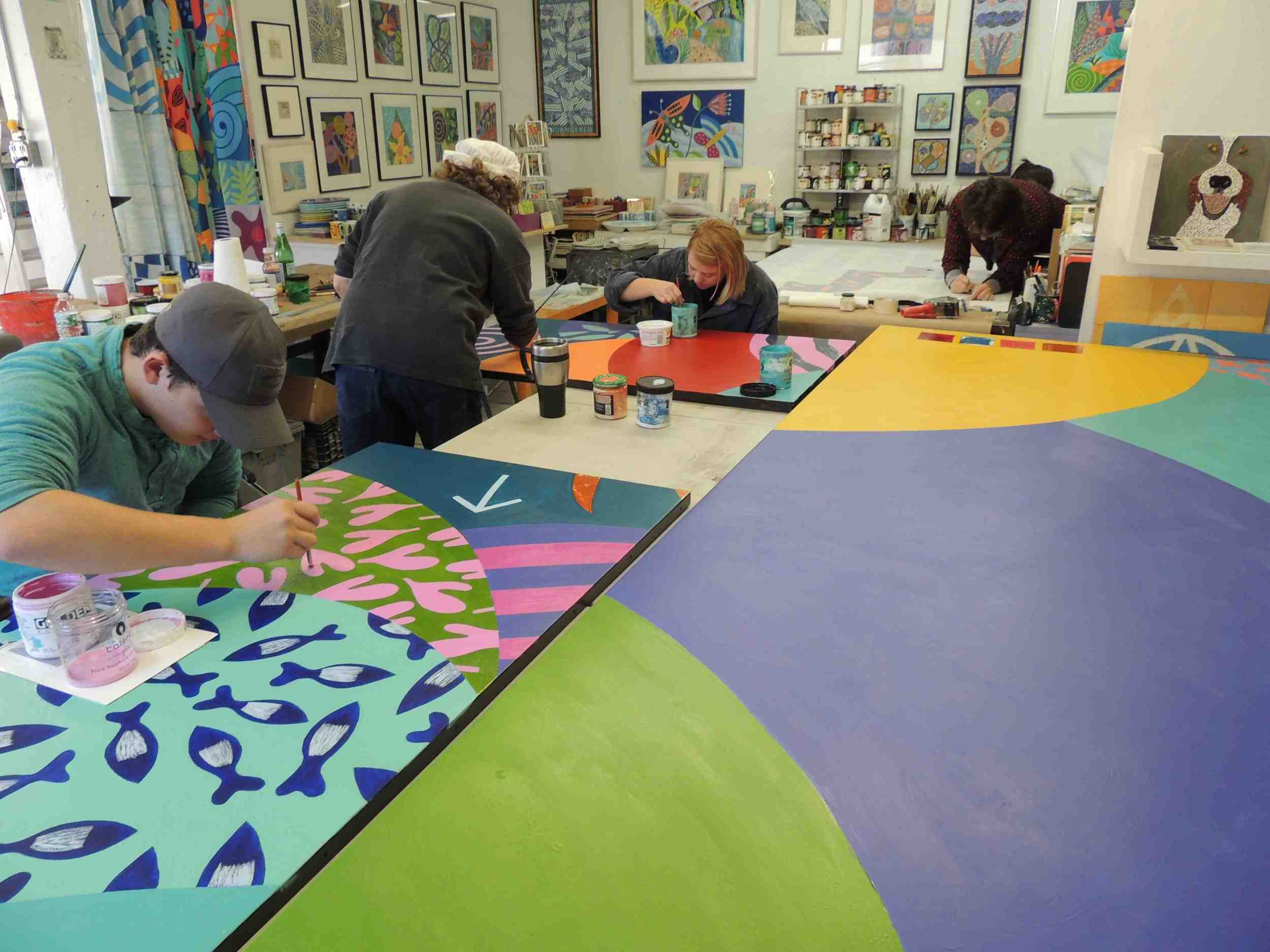 Harrison Ringel, Regina Gaudette, Carla Hauck and Rachel Newsam work on the details of the mural. Two coats of acrylic paint were applied to all areas.