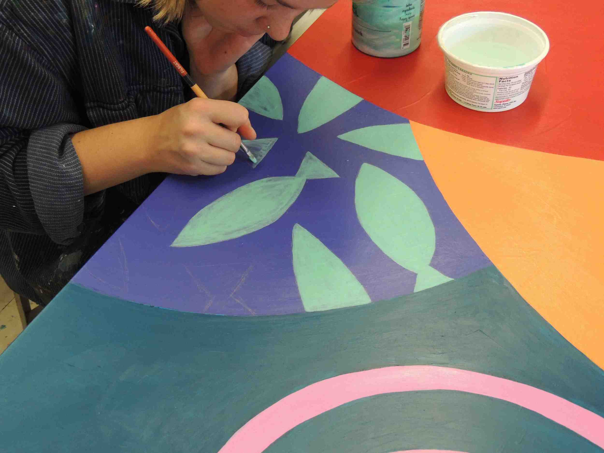 Carla Hauck applies the first coat of paint to a green school of fish.