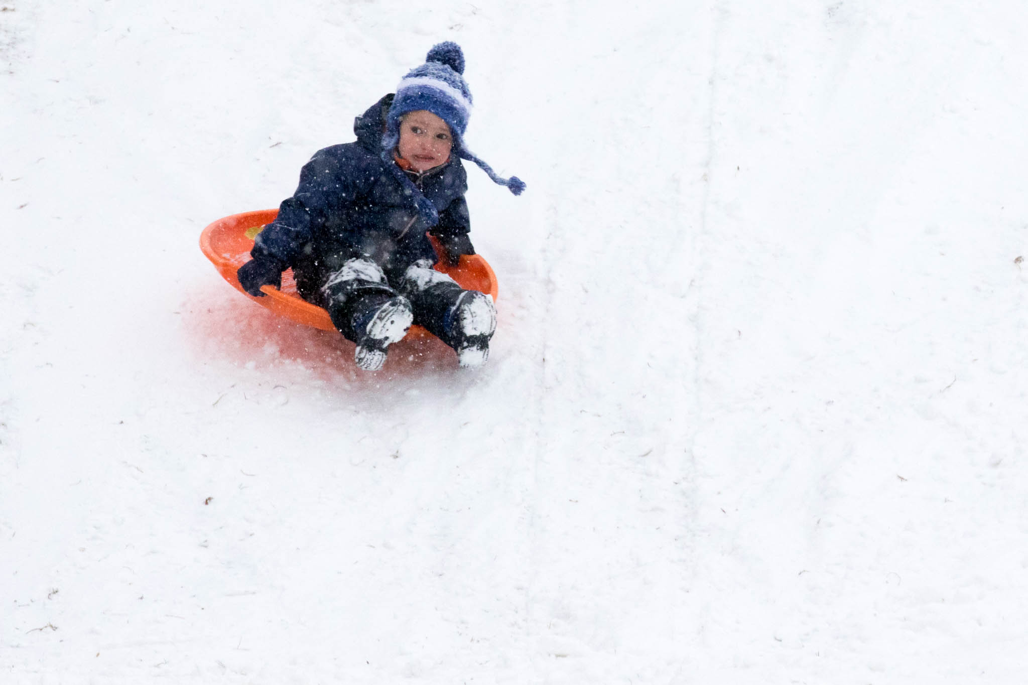 Child not entirely happy about riding a sled