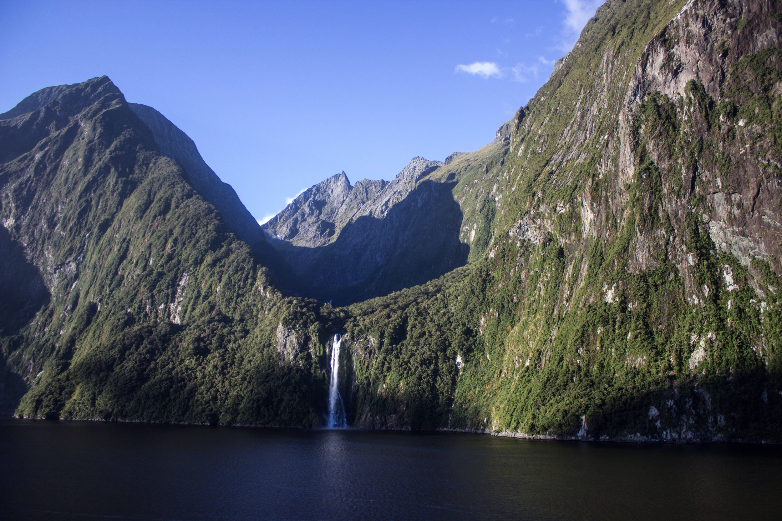 Stirling Falls dwarfed beneath the cliffs of The Lion and The Elephant. Milford Sound, New Zealand.